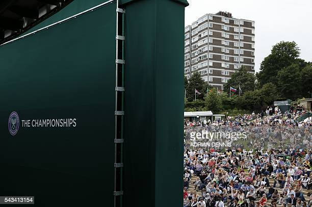 Spectators on Murray Mount watch the big screen as Britain's Andy Murray plays against Britain's Liam Broady during their men's singles first round...