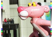 Spectators on the balcony of a building in New York's Times Square watch as the Pink Panther balloon floats by during the annual Macy's Thanksgiving...