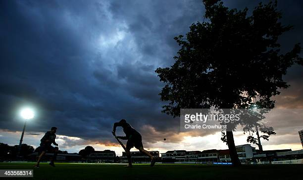 Spectators play cricket using the tree as a stump during a rain break under the evening sky during Royal London OneDay Cup match between Kent...