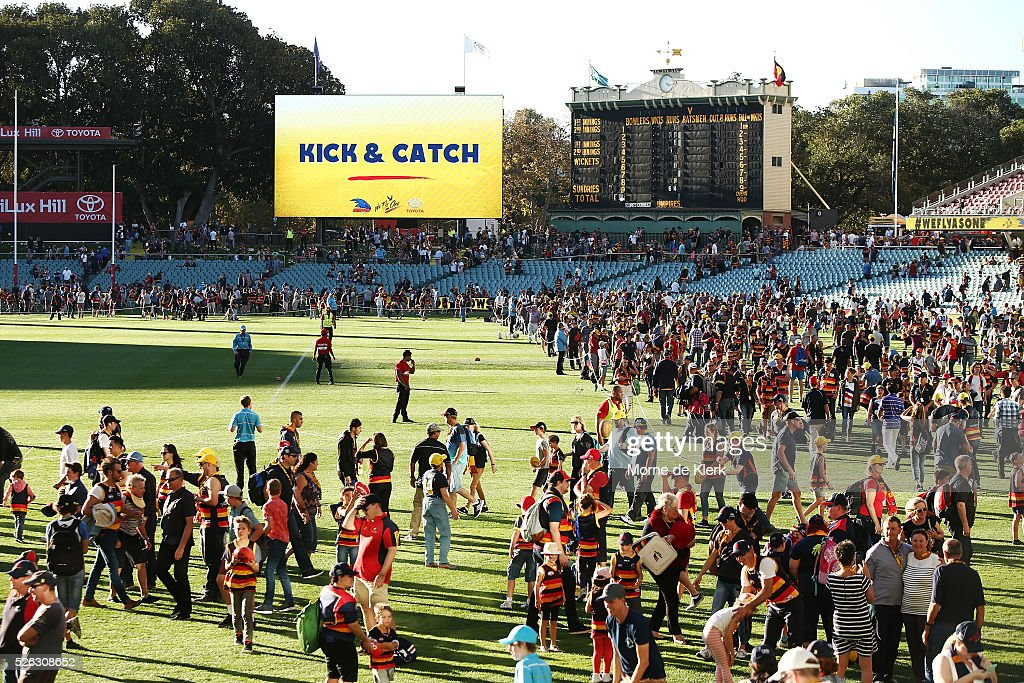 Spectators play kick and catch on the ground after the round six AFL match between the Adelaide Crows and the Fremantle Dockers at Adelaide Oval on April 30, 2016 in Adelaide, Australia.