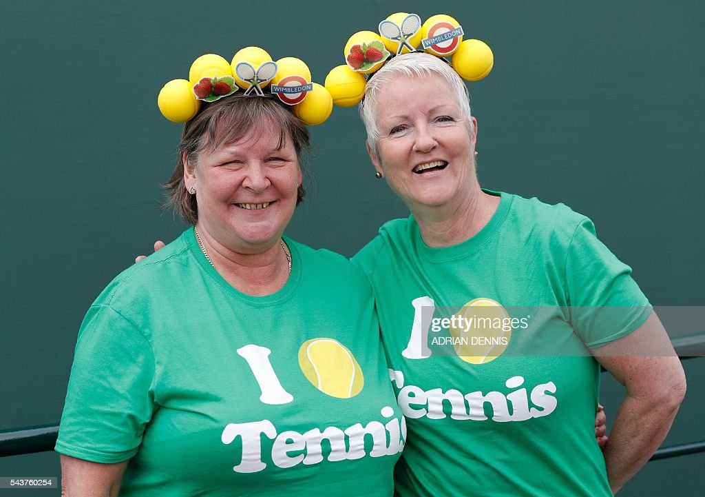 Spectators pose at the start of play on the fourth day of the 2016 Wimbledon Championships at The All England Lawn Tennis Club in Wimbledon, southwest London, on June 30, 2016. / AFP / ADRIAN