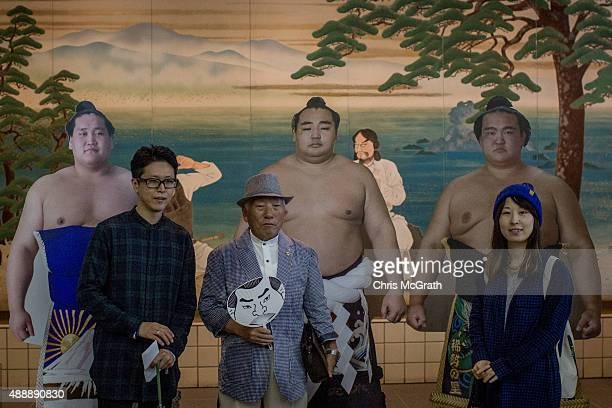 Spectators pose for pictures in front of cardboard cutouts of sumo wrestlers during the Tokyo Grand Sumo tournament at the Ryogoku Kokugikan on...