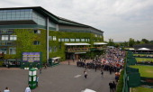 Spectators queue to be released into the grounds of the All England Club for day three of the 2013 Wimbledon Championships tennis tournament in...