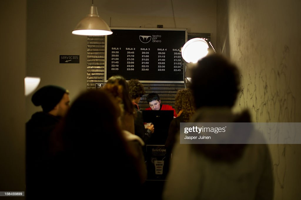 Spectators queue up to buy a ticket for a one of the micro theater shows at the 'Micro Teatro por Dinero' on December 15, 2012 in Madrid, Spain. In November 2009, fifty artists presented a theatre project in the thirteen rooms of a former brothel, two weeks before its demolition, with each function lasting less than 10 minutes. The initiative was a huge success, with more people queueing up outside than could enter. Today's 'Micro Theatre For Money' is named after the former brothel on Ballesta Street, and offers a cheap and original way for going out at night, especially in times of financial hardship. With each show priced at 4 Euros, over 150,000 spectators have already attended performances at the tiny theatre in the Malasana area. Anyone can submit a project to be chosen to perform for a month in one of the five tiny rooms in the basement of the theatre, making it an ideal platform for young Spanish authors and actors, often unemployed, to perform.