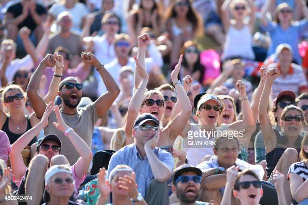 Spectators react as they watch a giant screen showing the men's semifinal match between Switzerland's Roger Federer and Britain's Andy Murray from...