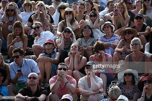 Spectators react as they watch a large screen television showing the Gentlemen's semifinal match between Andy Murray of Great Britain and Roger...