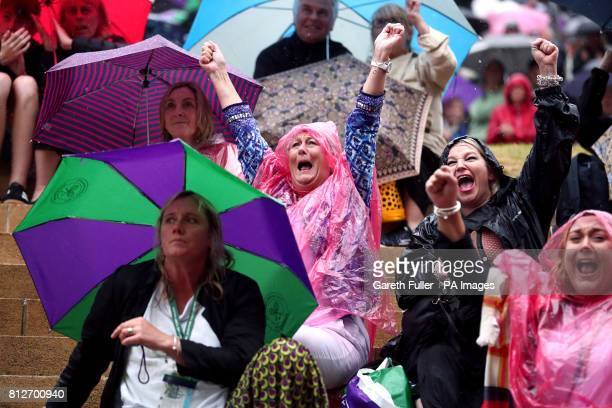 Spectators react as they watch Johanna Konta against Simona Halep on the big screen on Murray Mound on day eight of the Wimbledon Championships at...
