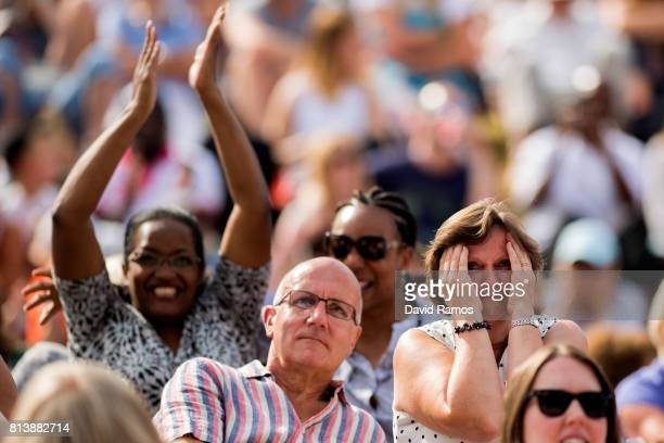 Spectators react as they watch the action on the screen from 'Murray Mound' during the Ladies Singles semi final match between Johanna Konta of Great...