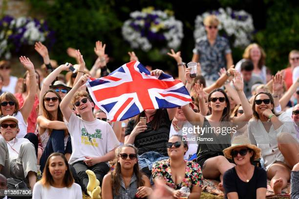 Spectators react as they watch the action on the screens from 'Murray Mound' during the Ladies Singles semi final match between Johanna Konta of...