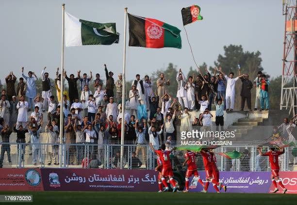 Spectators react in the stands as Afghan footballers celebrate their 30 win against Pakistan at the Afghanistan Football Federation stadium in Kabul...