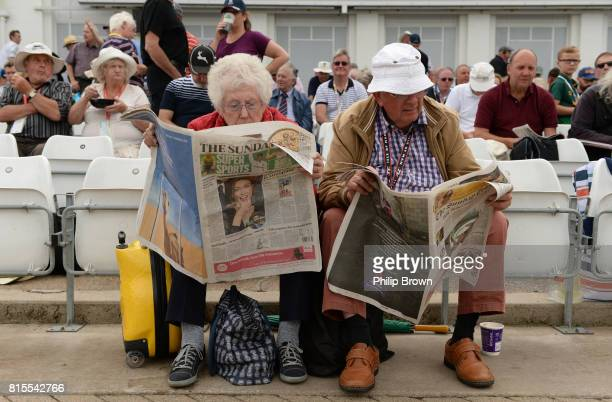 Spectators read rival Sunday newspapers during the lunch break on the third day of the 2nd Investec Test match between England and South Africa at...