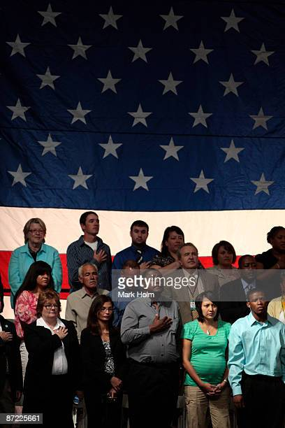 Spectators recite the Pledge of Allegiance before President Barack Obama addresses a crowd at the Rio Rancho High School gymnasium during a Town Hall...