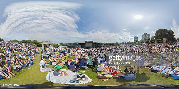 Spectators relax in the sun as they watch a match on a large television screen on Murray Mound on day four of the Wimbledon Lawn Tennis Championships...