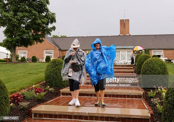 Spectators Rita Nyhoff and Lizz Green seek shelter from the rain during a weather delay in Round Three of the Senior PGA Championship presented by...