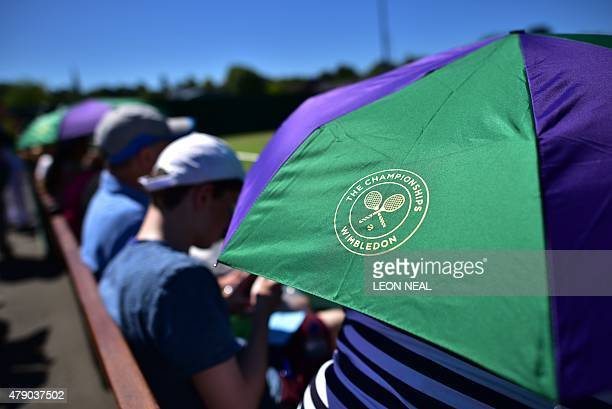 Spectators shade themselves from the sun on day two of the 2015 Wimbledon Championships at The All England Tennis Club in Wimbledon southwest London...