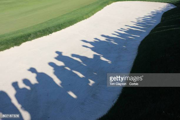 Spectators shadows on a sand trap on the eighteenth as they watch the closing stages of competition and Jordan Spieth's victory during the fourth...