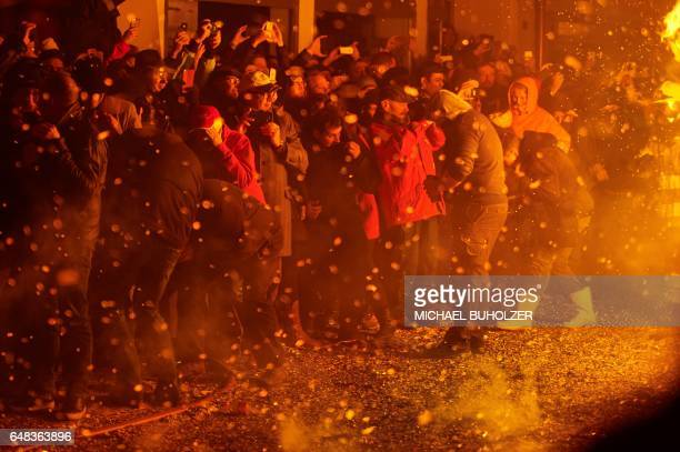 Spectators shelter from a burning wooden wagen during the 'Chienbase' procession on March 5 2017 in Liestal northern Switzerland The procession takes...