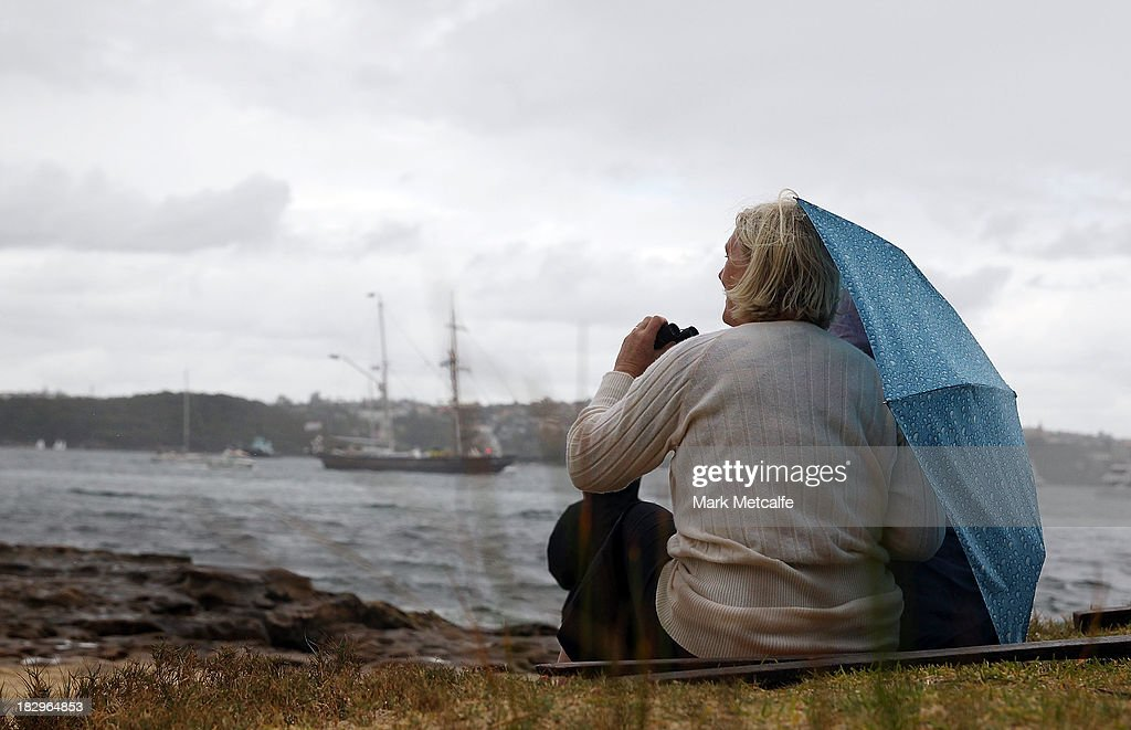 Spectators shelter from the rain as Tall Ships enter Sydney Harbour on October 3, 2013 in Sydney, Australia. Over 50 ships will participate in the International Fleet Review at Sydney Harbour to commemorate the 100 year anniversary of the Royal Australian Navy's fleet arriving into Sydney. Prince Harry will take part in the fleet review during his two-day visit to Australia.