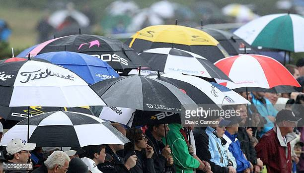 Spectators shelter from the rain during the first round of the 139th Open Championship on the Old Course St Andrews on July 15 2010 in St Andrews...