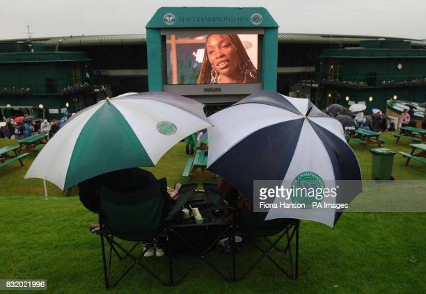 Spectators shelter from the rain on Henman Hill as a Venus Williams interview is displayed on the screen during the first day of the wimbledon...