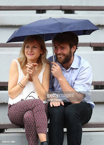 Spectators shelter from the rain under an umbrella during day one of the 2016 French Open at Roland Garros on May 22 2016 in Paris France