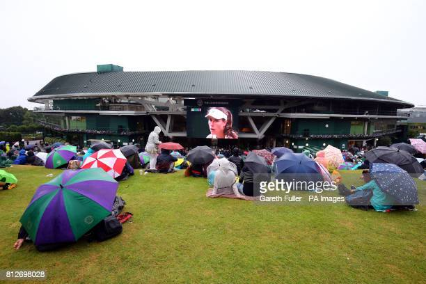 Spectators shelter from the rain under umbrellas as they watch Johanna Konta against Simona Halep on the big screen on Murray Mound on day eight of...