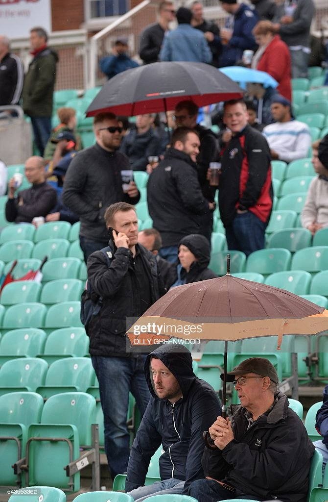 Spectators shelter from the rain under umbrellas during a rain delay in the fourth One Day International (ODI) cricket match between England and Sri Lanka at The Oval cricket ground in London on June 29, 2016. Rain stopped play at 1419 local time (1319 GMT) in the fourth one day international between England and Sri Lanka at The Oval, London on Wednesday. Sri Lanka had made 127-1 from 18.1 overs, with Danushka Gunathilaka 48 not out and Kusal Mendis 75 not out. ECB
