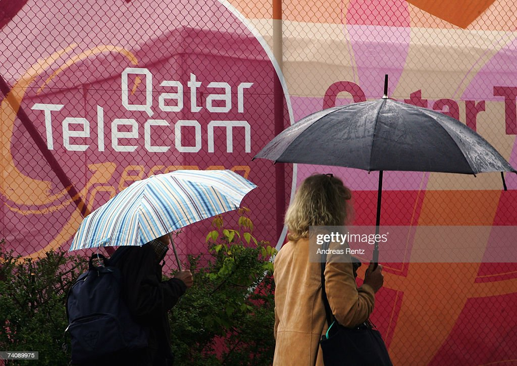 Spectators shelter from the rain under umbrellas during day one of the Women's Qatar Telecom German Open at the Rot Weiss Berlin tennis club on May 7...