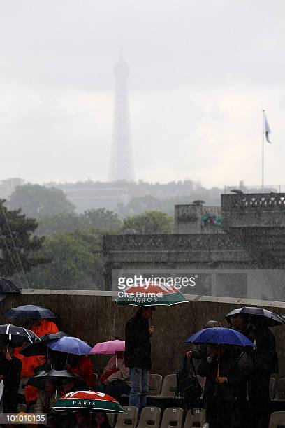 Spectators shelter from the rain with the Eiffel Tower in the background on day five of the French Open at Roland Garros on May 27 2010 in Paris...