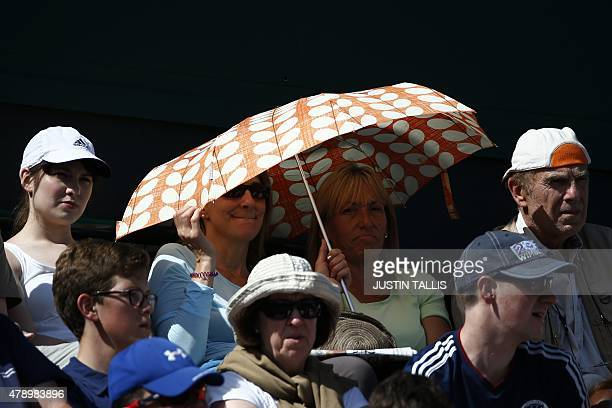 Spectators shelter under an umbrella from the sun as they watch Bulgaria's Tsvetana Pironkova play against Switzerland's Belinda Bencic during their...