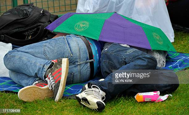 Spectators shelter under an umbrella on the grass at Murray Mount as rain holds up play on the outdoor courts on day five of the 2013 Wimbledon...