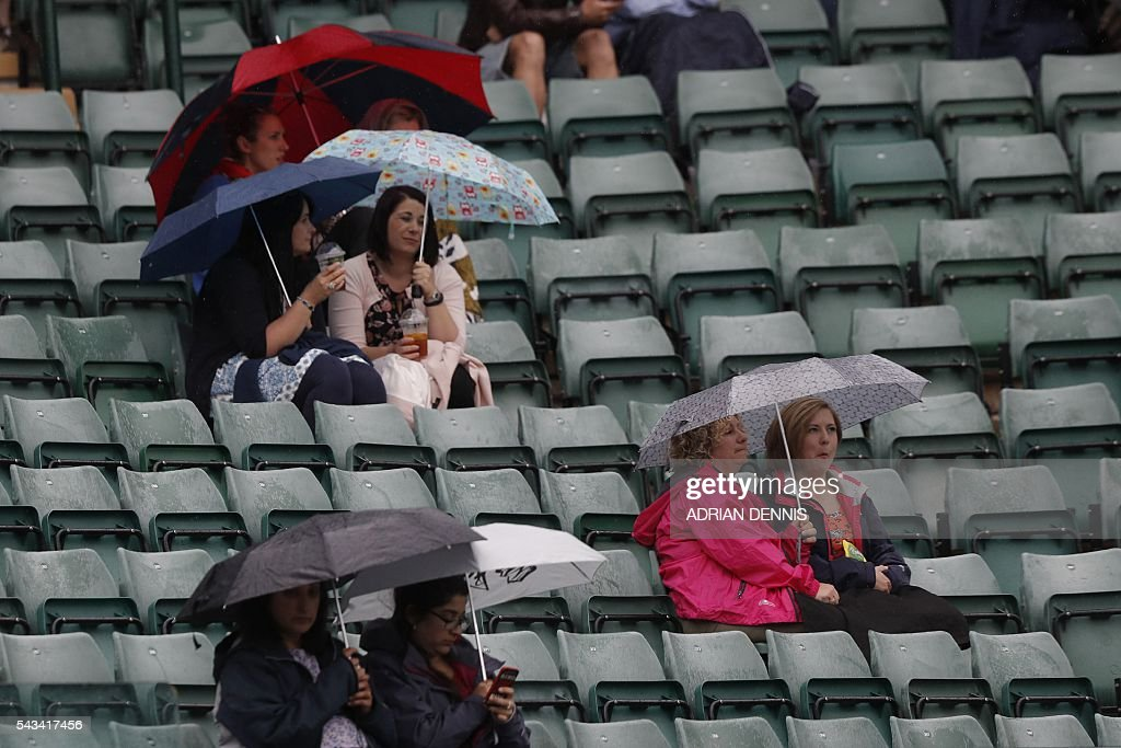 Spectators shelter under umbrellas after rain stopped play on the second day of the 2016 Wimbledon Championships at The All England Lawn Tennis Club in Wimbledon, southwest London, on June 28, 2016. / AFP / ADRIAN