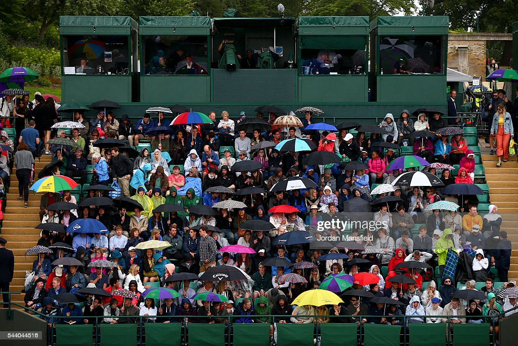 Spectators shelter under umbrellas as rain delays play during day four of the Wimbledon Lawn Tennis Championships at the All England Lawn Tennis and Croquet Club on July 1, 2016 in London, England.