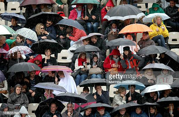Spectators shelter under umbrellas as rain starts to fall during day five of the French Open at Roland Garros on May 30 2013 in Paris France