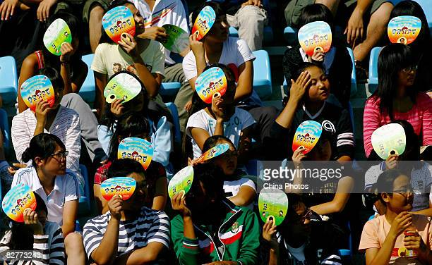 Spectators shield themselves from strong sunlight with fans while watching the FiveASide Football match between Argentina and Brazil at Olympic Green...