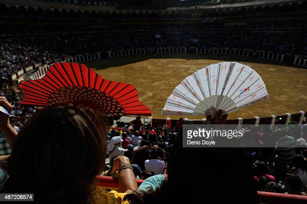 Spectators shield themselves from the sun's rays with fans at the start of the Liga de Corte Puro finals at the Plaza de Toros on September 6 2015 in...