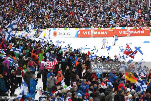 Spectators show their support as Stina Nilsson of Sweden and Krista Parmakoski of Finland race to the finish line during the Women's Cross Country...
