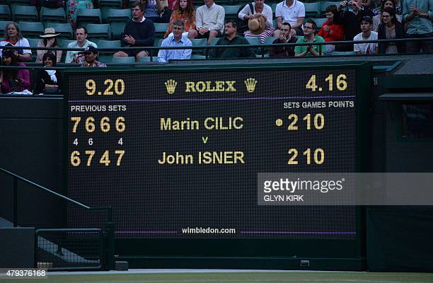 Spectators sit above the score board after the men's singles third round match between Croatia's Marin Cilic and US player John Isner was postponed...