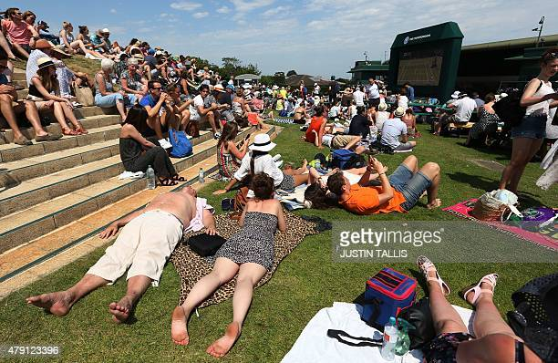 Spectators sit and lie in the sunshine on Murray Mount at The All England Tennis Club on day three of the 2015 Wimbledon Championships in Wimbledon...