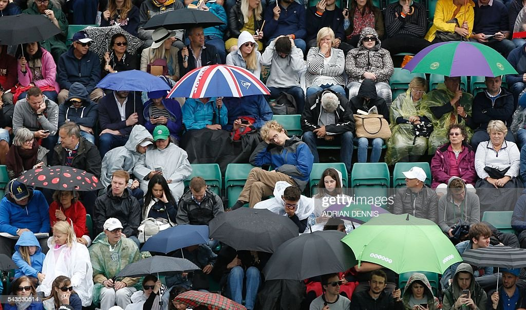 Spectators sit and wait as rain halts the start of the third day of the 2016 Wimbledon Championships at The All England Lawn Tennis Club in Wimbledon, southwest London, on June 29, 2016. / AFP / ADRIAN
