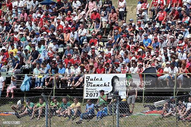Spectators sit behind a banner reading 'Jules Bianchi Ferrari World Champion 2017' in tribute to late French Formula One driver Jules Bianchi who...