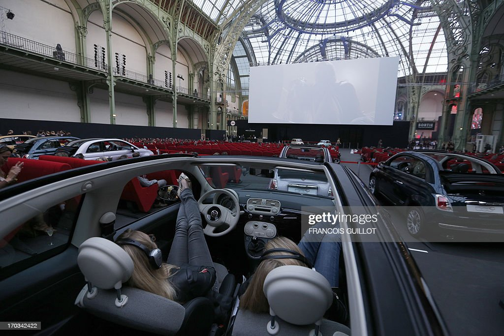 Spectators sit in an Italian car as they watch The Big Lebowski at the Grand Palais in Paris, on June 11, 2013, during the Cinema Paradiso, the transformation of the Grand Palais into a giant indoor drive-in replica by French cinema company MK2, that takes place from June 10 to June 21.