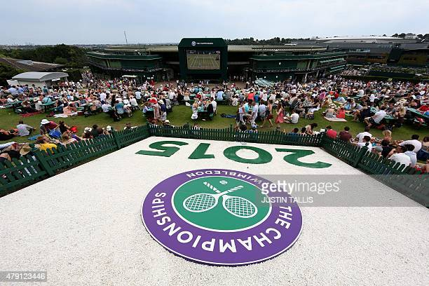 Spectators sit on Murray Mount at The All England Tennis Club on day three of the 2015 Wimbledon Championships in Wimbledon southwest London on July...
