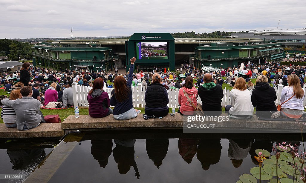 Spectators sit on the edge of a pond at the top of Murray Mount on day one of the 2013 Wimbledon Championships tennis tournament at the All England Club in Wimbledon, southwest London, on June 24, 2013.