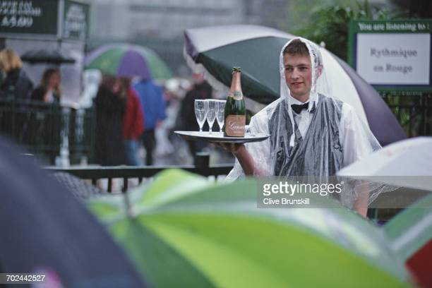 Spectators sit under their umbrellas around the covered courts and a waiter delivers champagne as rain delays play at the Wimbledon Lawn Tennis...