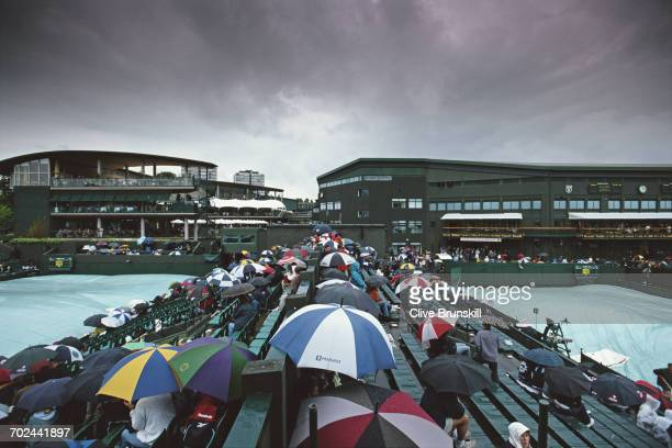 Spectators sit under their umbrellas around the covered courts as rain delays play at the Wimbledon Lawn Tennis Championship on 3 July 2002 at the...