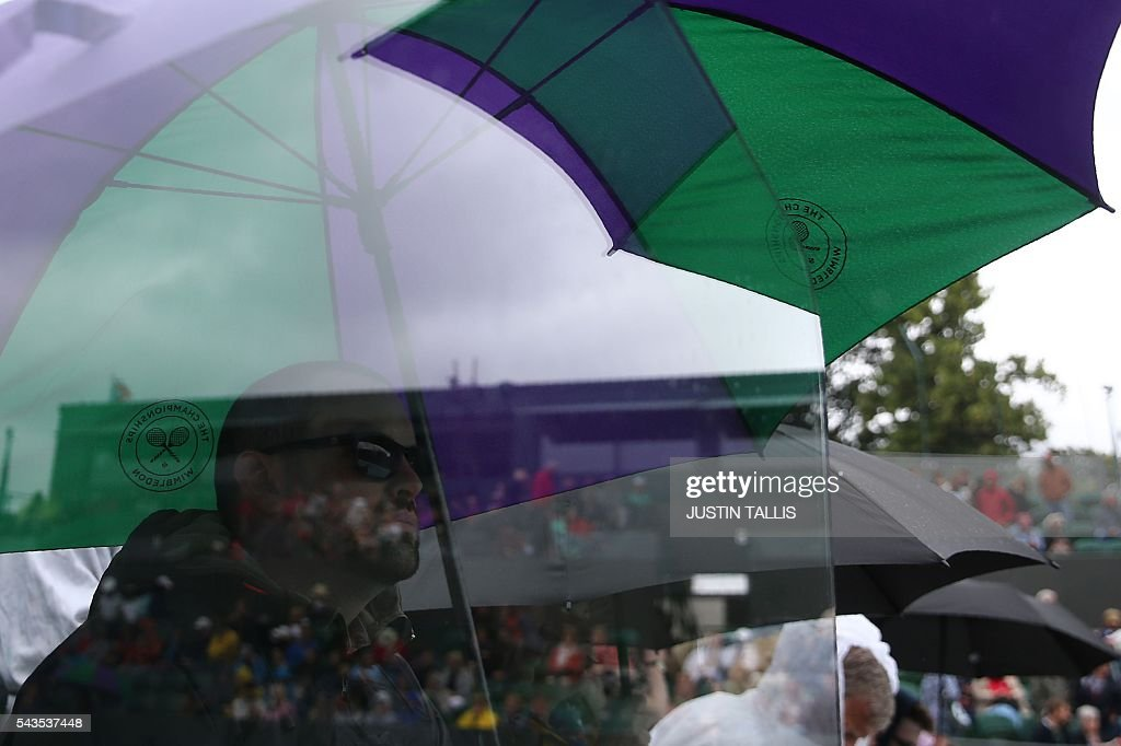 Spectators sit under umbrellas on court 2 as rain stops play during the third day of the 2016 Wimbledon Championships at The All England Lawn Tennis Club in Wimbledon, southwest London, on June 29, 2016. / AFP / JUSTIN