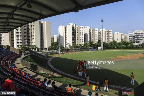 Spectators sit while a team gathers on the field of a cricket stadium in Palava City on the outskirts of Mumbai India on Thursday May 25 2017 Lodha...