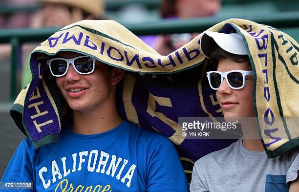 Spectators sit with a towel on their heads to shade them from the Sun as they wait for play to commence on Court One on day three of the 2015...