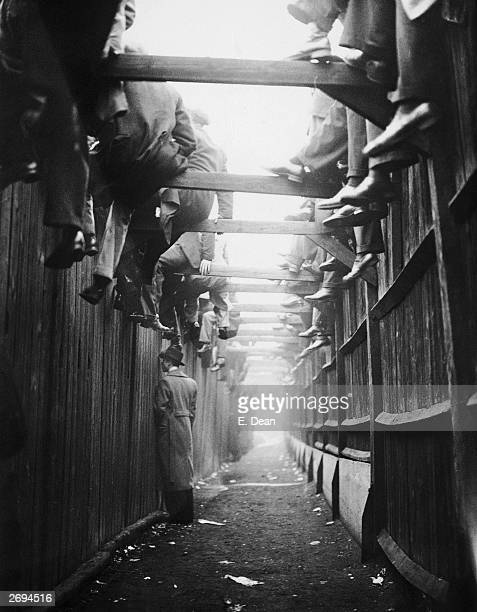 Spectators sitting on barriers at the third round FA Cup game between Millwall and Manchester City at the Den